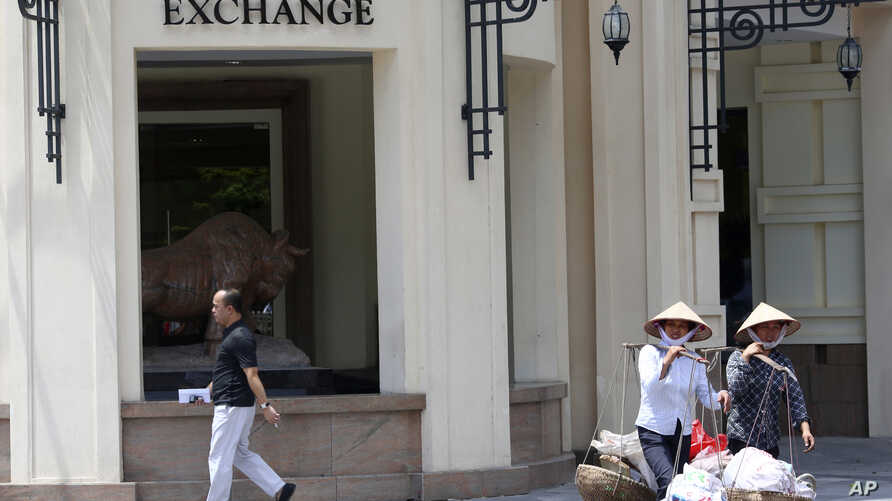 FILE- People walk by the Hanoi Stock Exchange in Hanoi, Vietnam on  Sept. 10, 2012.