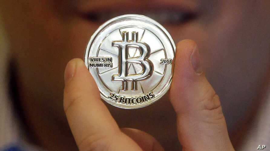 FILE - A man holds a token beaing the symbol of a cryptocurrency at his shop in Sandy, Utah. The tiny Marshall Islands is creating its own digital cryptocurrency in order to raise hard cash to pay bills and boost the economy.