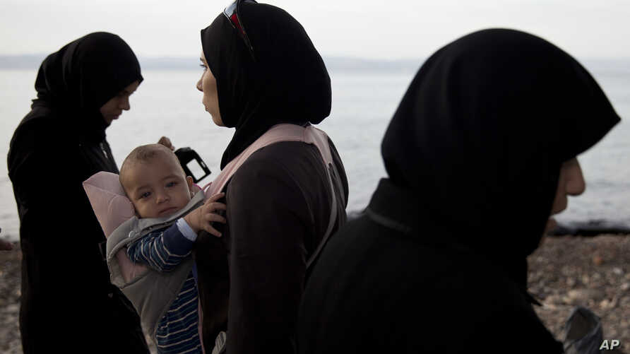 A veiled woman refugee holds her child after arriving with others on a dinghy from Turkey at Lesbos Island, Greece, Sept. 9, 2015.