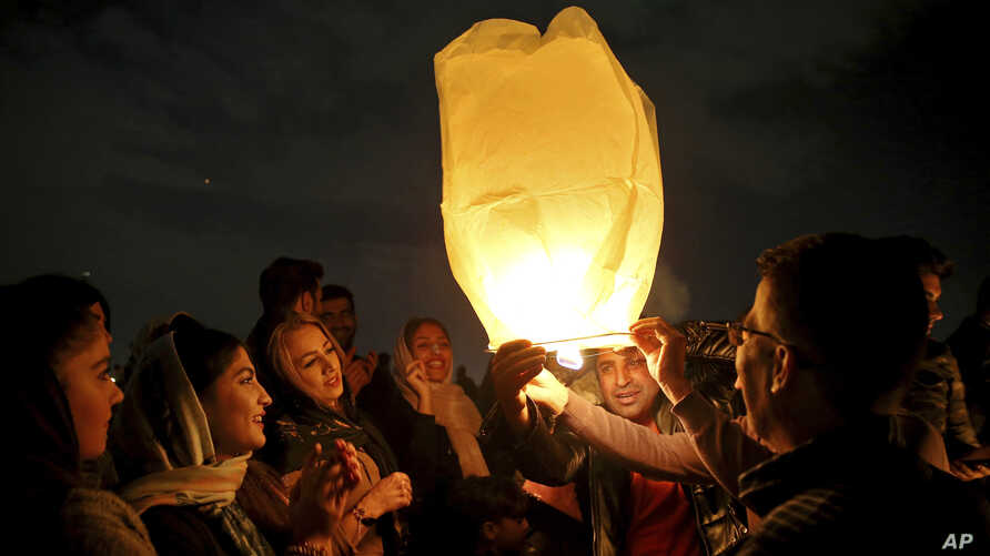 """Iranians release a lit lantern during a celebration, known as """"Chaharshanbe Souri,"""" or Wednesday Feast, March 19, 2019, marking the eve of the last Wednesday of the solar Persian year, in Tehran."""