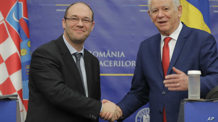 Croatia's Minister of Foreign and European Affairs Davor Ivo Stier, left, shakes hands with Romanian Foreign Minister Teodor Melescanu after a press briefing in Bucharest, Romania, March 14, 2017.