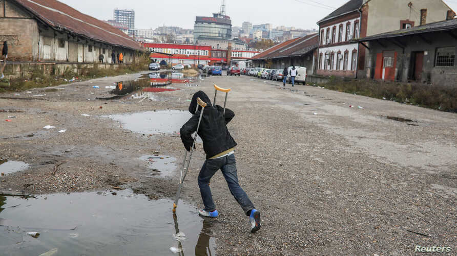 A migrant plays with crutches in front of a derelict customs warehouse in Belgrade, Serbia, November 10, 2016.