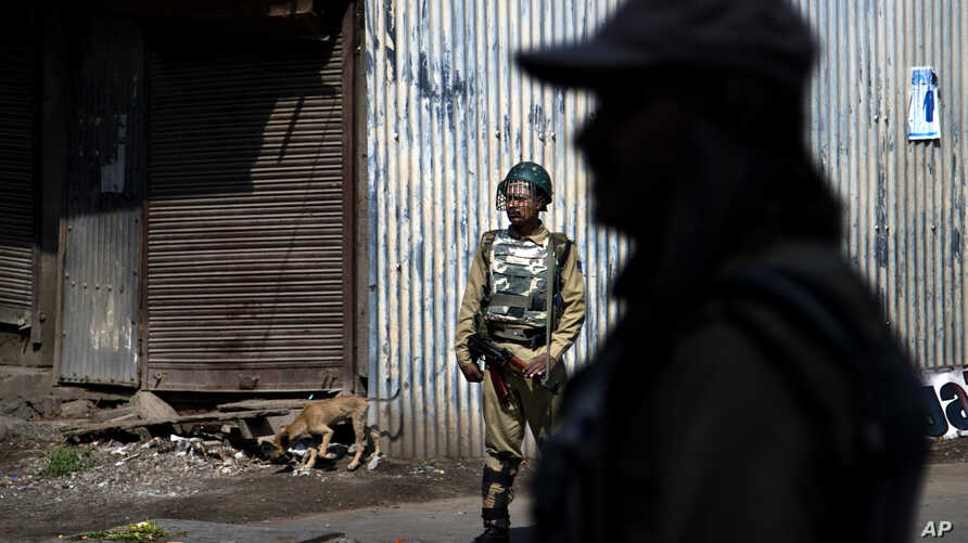 Indian paramilitary soldiers stand guard during a curfew in Srinagar, Indian controlled Kashmir, Friday, July 29, 2016.