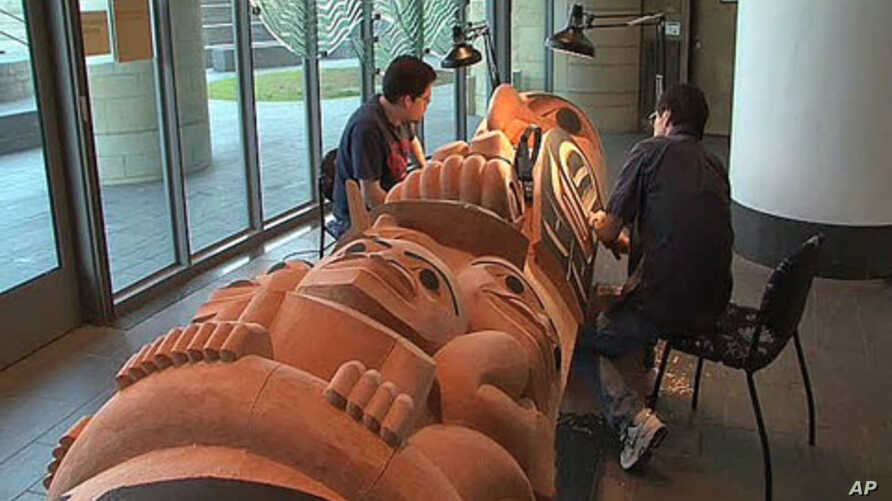Native American artist David Boxley is from the Tsimshian tribe in Alaska, and he and his son work on one of the many totem poles they have created to keep their native culture alive, at the National Museum of the American Indian in Washington, DC, J