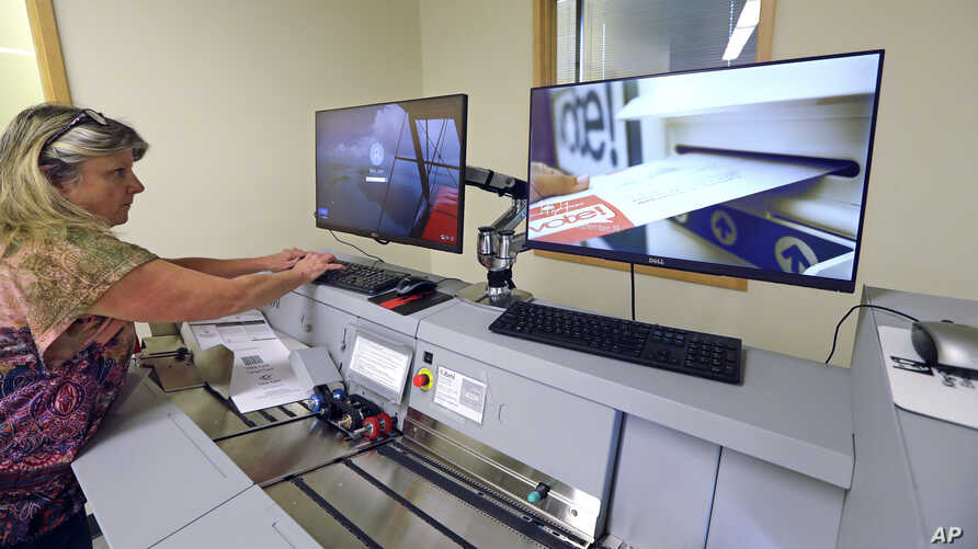 FILE - Election worker Kelly Moselage puts test ballots through a vote-counting machine at the King County elections office in Renton, Wash., Sept. 19, 2018.