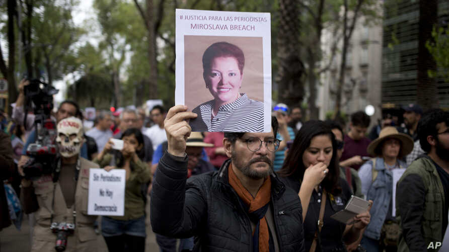A man holds up a photo of Mexican journalist Miroslava Breach, gunned down in the northern state of Chihuahua on March 23, 2017, during a march in Mexico City, March 25, 2017. Breach was the third journalist to be killed this month in Mexico.
