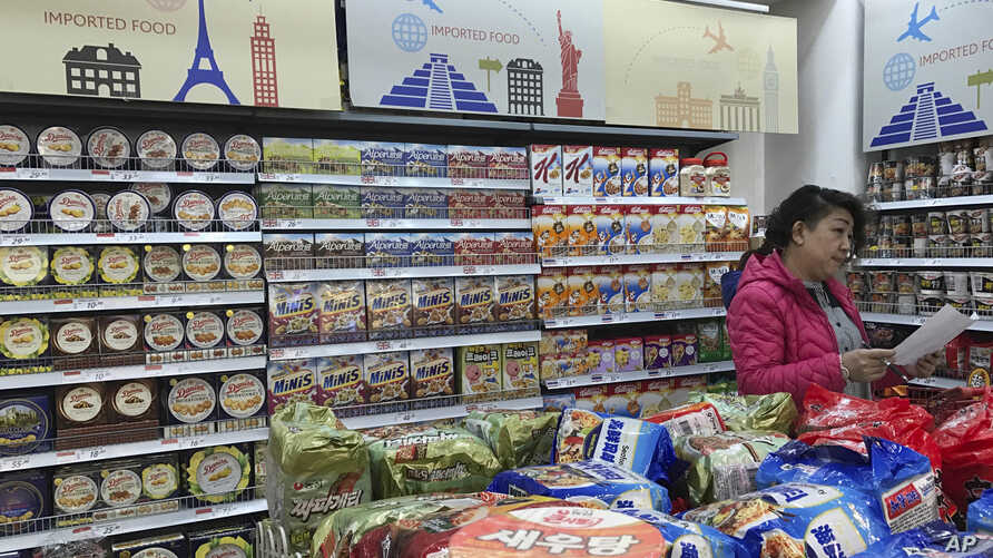 FILE - In this photo taken March 17, 2017, a vendor takes stock of imported food at a mall in Beijing, China.