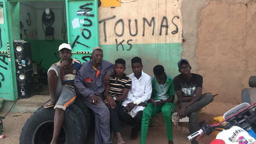 Abdoul Ahmed (second from left) pictured outside his mechanic shop with his apprentices, Agadez, Niger, Feb. 20, 2018.