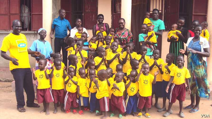 Mama Susan Tabia and some of the orphans under her care in front of the new facility just outside Adjumani town in northern Uganda. (S.P. Apiku/VOA)