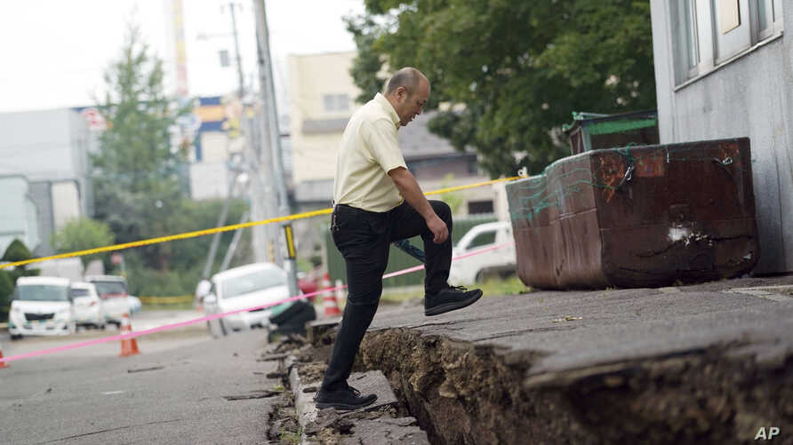 A man walks over ground that shifted in an earthquake in Kiyota, on the outskirts of Sapporo, Hokkaido, northern Japan, Sept. 7, 2018.