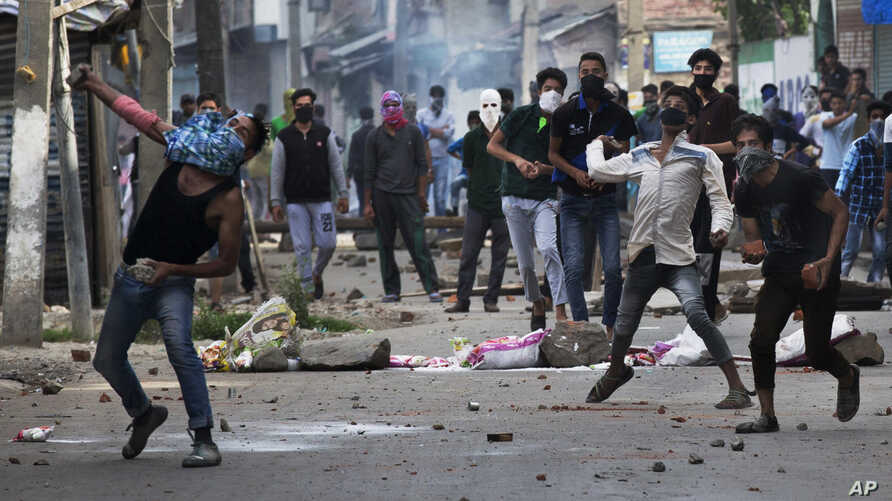 Kashmiri Muslim protesters throw stones at Indian security personnel during a protest in Srinagar, Indian-controlled Kashmir, Aug. 9, 2016.
