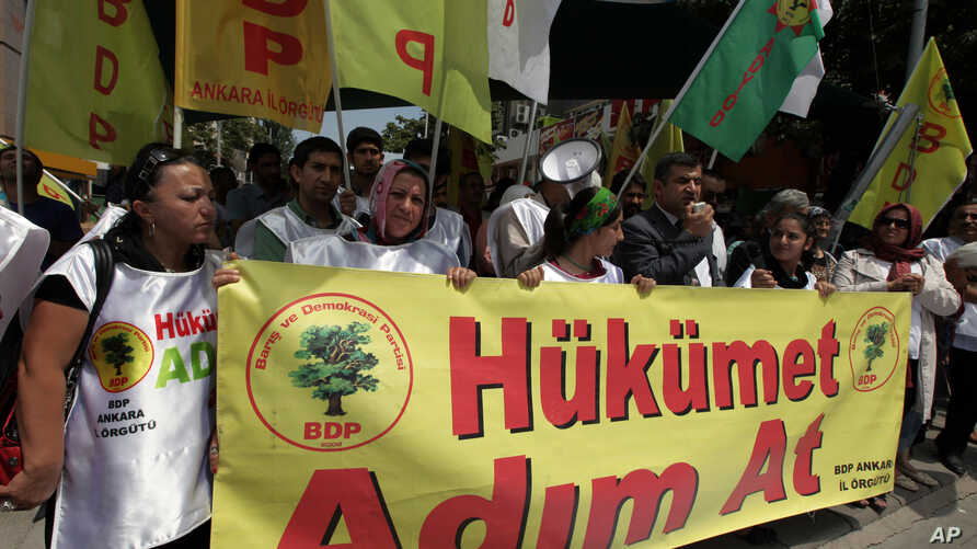 """Kurds hold a banner that reads """" government, take steps """" during a protest in Ankara, Turkey. Kurdish rebels on Friday gave Turkey a """"final warning"""" to take steps that would move forward peace talks aimed at ending a 30-year old conflict that has cla"""
