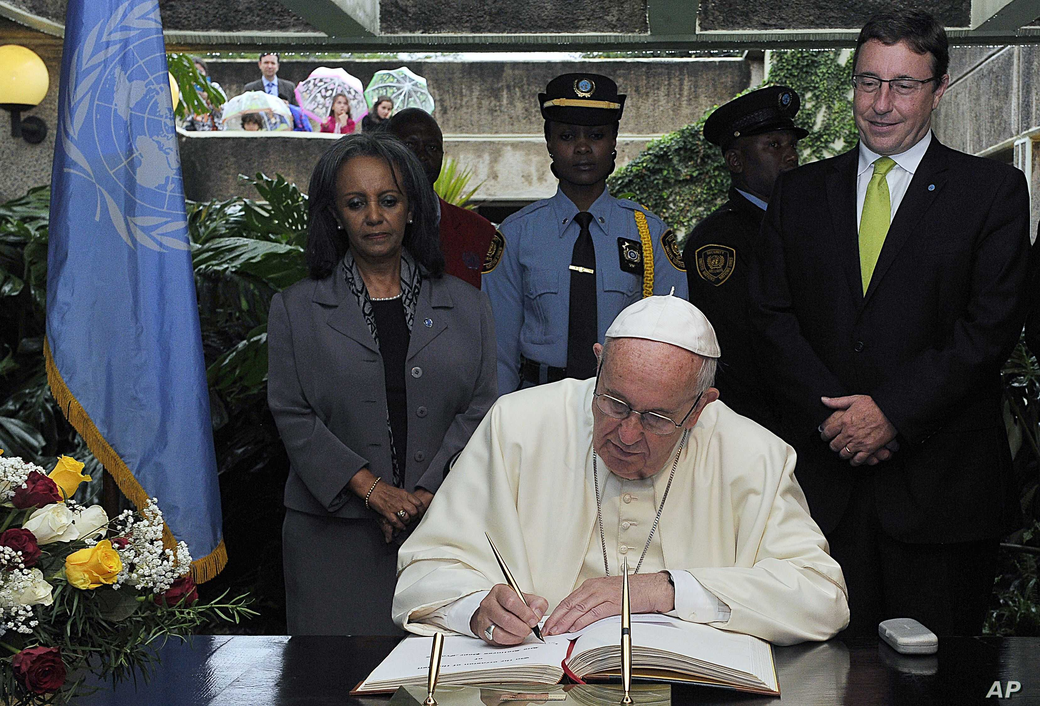 With Achim Steiner, executive director of the U.N. Environment Program, right, looking on, Pope Francis signs the visitors book at the United Nations regional office in Nairobi, Kenya, Nov. 26, 2015.