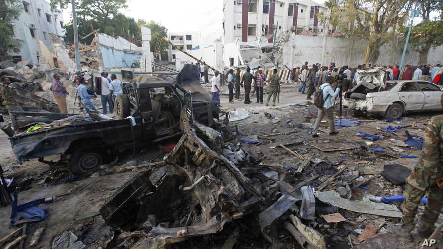 Rescue workers stand near the wreckage of vehicles in Mogadishu, Somalia, Oct 29, 2017, after a car bomb was detonated  Saturday night. A Somali police officer said security forces ended a nightlong siege at a Mogadishu hotel by attackers who stormed