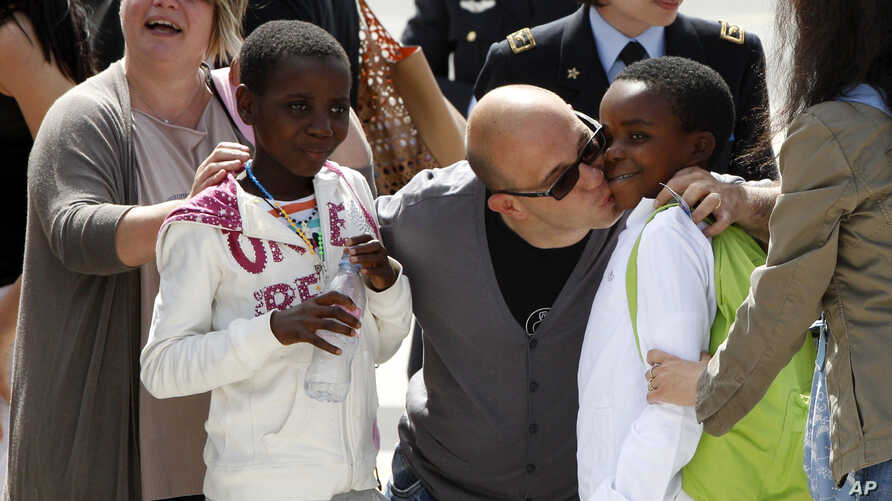 FILE - Congolese children are welcomed by their Italian adoptive relatives as they disembark after landing from Kinshasa, at Ciampino's military airport, on the outskirts of Rome, May 28, 2014.