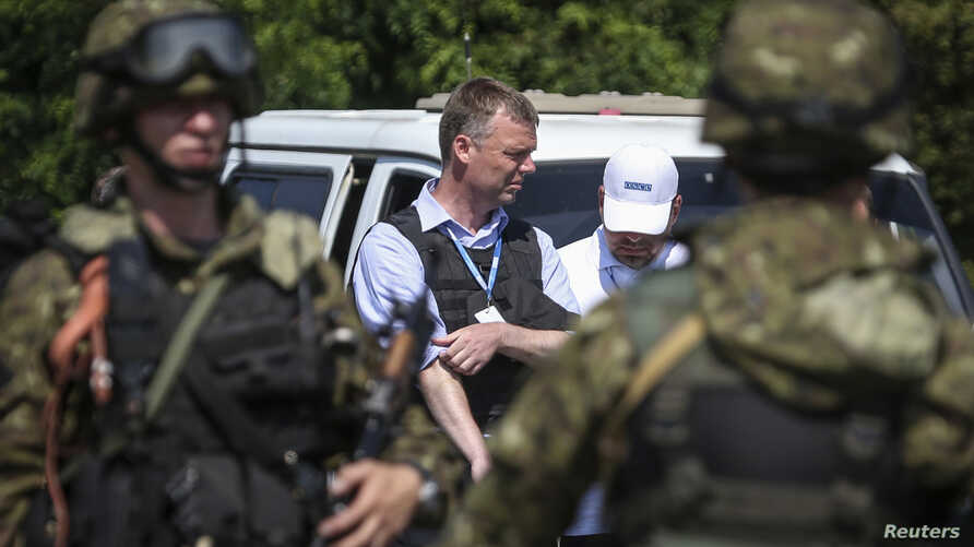 Alexander Hug (C), deputy head for the Organisation for Security and Cooperation in Europe's (OSCE) monitoring mission in Ukraine, looks on next to armed pro-Russian separatists on the way to the site in eastern Ukraine where the downed Malaysia Airl...