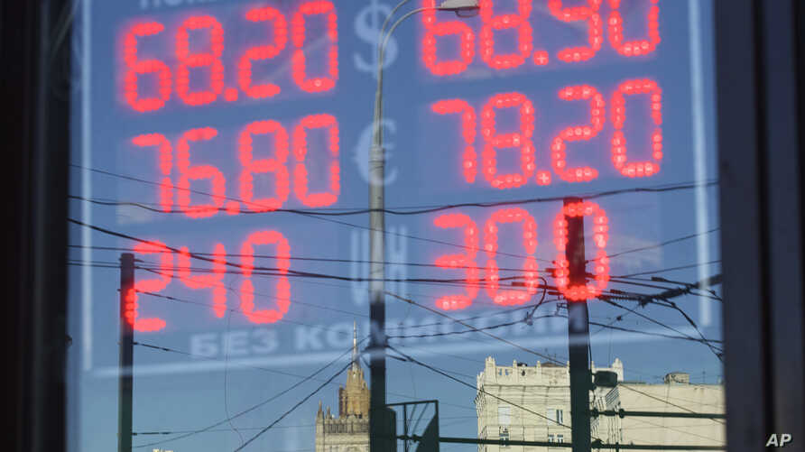 FILE - The building of the Russian Foreign Ministry, center back, is reflected in a sign showing currency exchange rates in Moscow, Russia, Aug. 21, 2015.