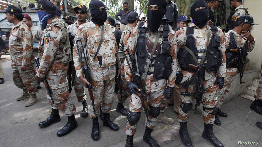 Paramilitary soldiers stand guard, as they present men (unseen), who were detained during Wednesday's raid on the Muttahida Qaumi Movement (MQM) political party headquarters, before an anti-terrorism court in Karachi, March 13, 2015.
