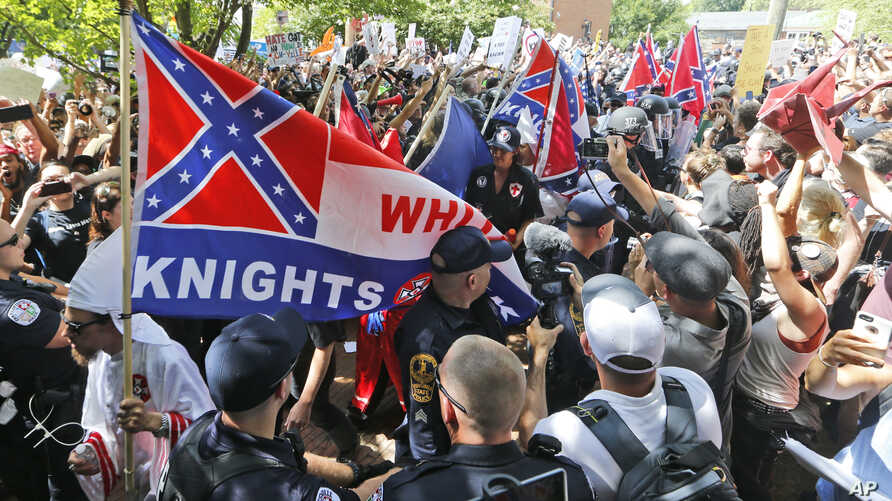 FILE- Members of the white supremacist KKK are escorted by police past a large group of protesters during a KKK rally in Charlottesville, Virginia, July 8, 2017.