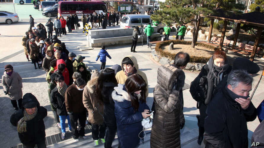 South Koreans wait in line to cast their votes in a presidential election at a polling station in Seoul, South Korea, December 19, 2012.