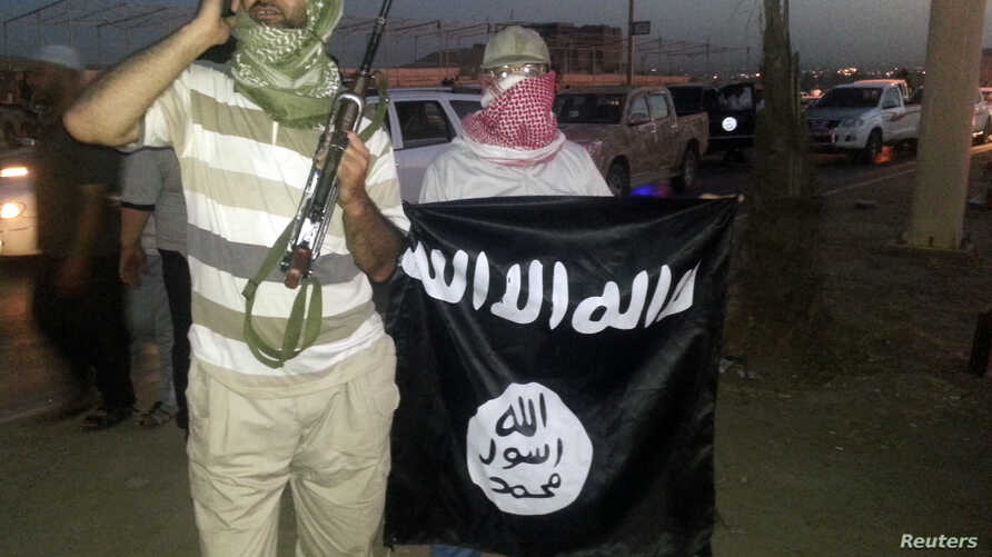 A fighter of the Islamic State of Iraq and the Levant (ISIL) holds a weapon while another holds a flag in the city of Mosul, June 23, 2014.