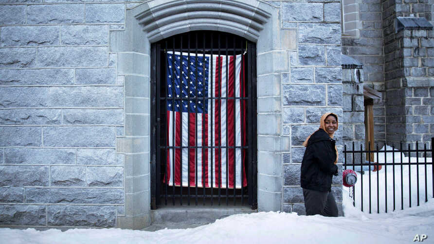 A U.S. flag hangs at the Franco American Heritage Center as a woman enters to attend the local high school's pre-prom fashion show in Lewiston, Maine, Thursday, March 16, 2017.