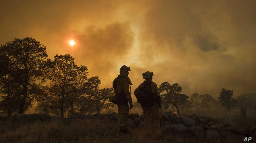 Firefighter Jake Hainey, left, and engineer Anna Mathiasen watch as a wildfire burns near Oroville, Calif., July 8, 2017. The fast-moving wildfire in the Sierra Nevada foothills destroyed structures, including homes, and led to several minor injuries