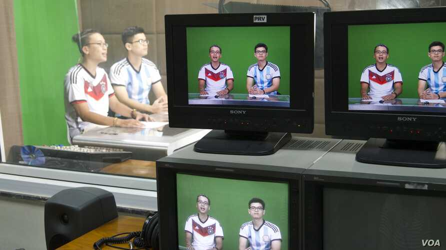 """""""Rappers Vo Viet Phuong, 25, and Nguyen Trong Duc, 27, record the latest edition of Rap News Plus at Vietnam News Agency's television studio in central Hanoi, Vietnam, July 15, 2014. (Marianne Brown)"""