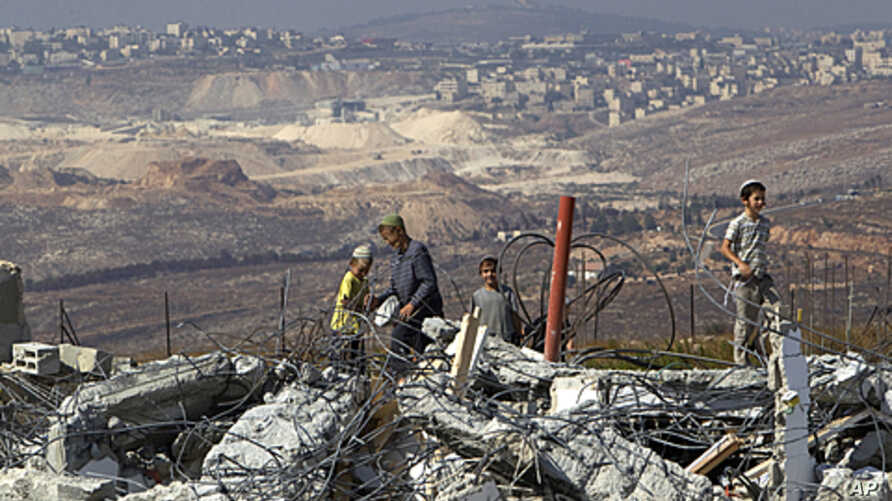 Jewish settler boys stand atop ruins of razed buildings in the unauthorized Jewish hilltop outpost of Migron, near the West Bank city of Ramallah, September 5, 2011.