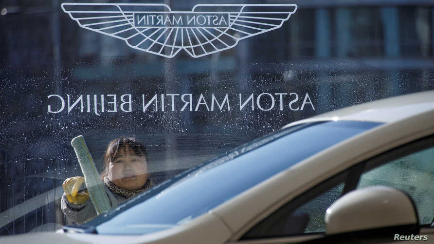A woman cleans the window at a Aston Martin luxury car dealership in Beijing, Dec. 12, 2018.