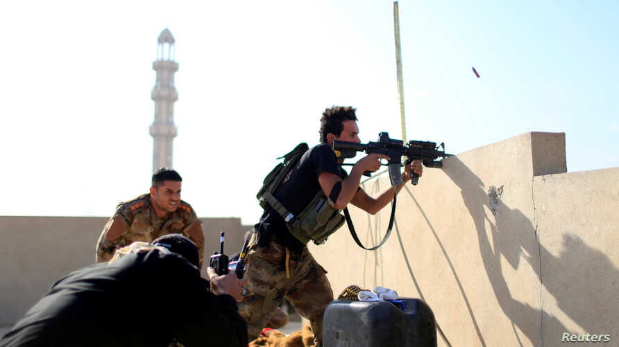 Member of the Iraqi Counter Terrorism Service fires his weapon at Islamic State militants in the al-Zahraa neighborhood of Mosul, Iraq, Nov. 13, 2016.