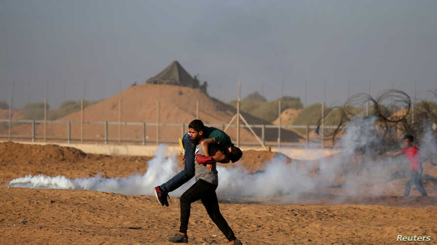 A wounded Palestinian is evacuated during a protest calling for lifting the Israeli blockade on Gaza and demanding the right to return to their homeland, at the Israel-Gaza border fence, in the southern Gaza Strip, Sept. 21, 2018.