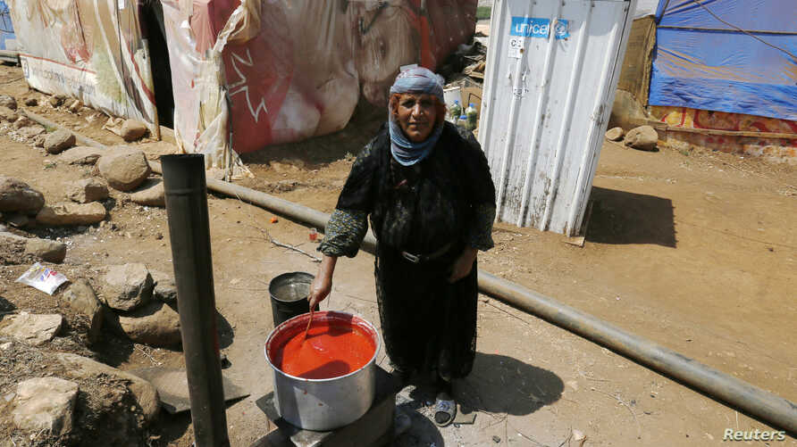 A Syrian woman cooks in front of her tent after she and her family fled from Raqqa in Syria, in Wazzani village in south Lebanon Aug. 30, 2014.
