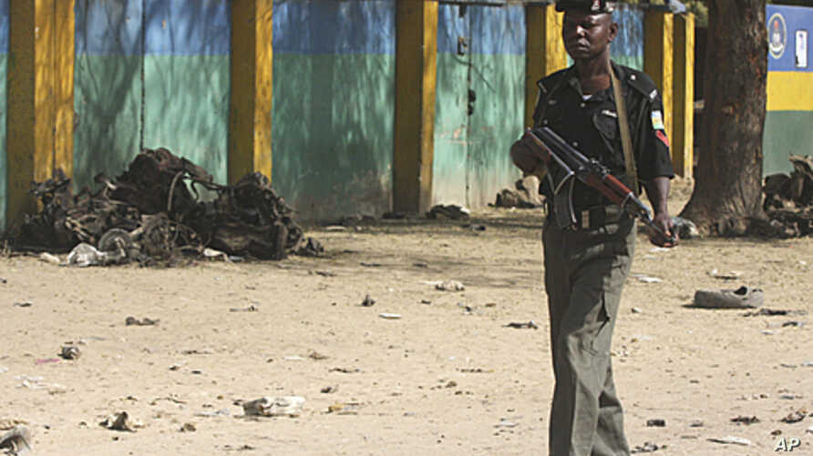 A police officer walks past an engine block of a suicide bomber's vehicle by the wall of the state police headquarters in Kano, Nigeria, January 24, 2012.