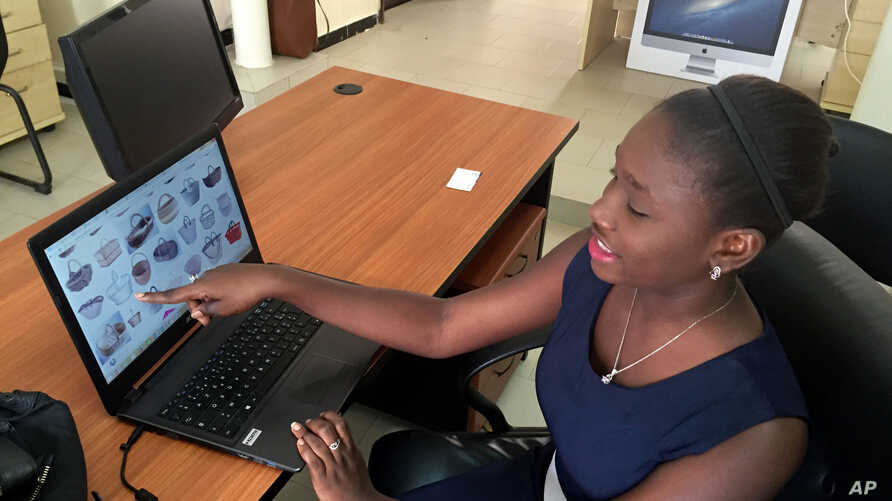 Design engineering graduate Youma Fall shows pictures of baskets, the inspiration for another app she might later pursue to help women sell local products from her PayDunya office in Dakar, Senegal, Sept. 7, 2016.