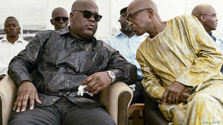 Felix Tshisekedi (L) talks to an unidentified visitor as he mourns the death of his father and veteran Congolese opposition leader Etienne Tshisekedi, in the courtyard of his residence in the Limete Municipality of the Democratic Republic of Congo's