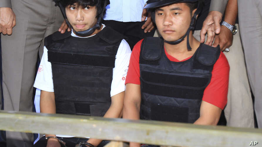 Workers from Myanmar, Saw, left, and Win, sit together, escorted by a Thai police officer, during a press conference in Koh Tao island, Surat Thani province, Thailand, Friday, Oct. 3, 2014.