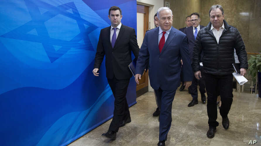 File - In this Sunday, March 11, 2018 file photo Israeli Prime Minister Benjamin Netanyahu, escorted by his spokesman David Keyes, left, arrives for the weekly cabinet meeting at his office in Jerusalem. An Israeli opposition lawmaker on Sunday calle