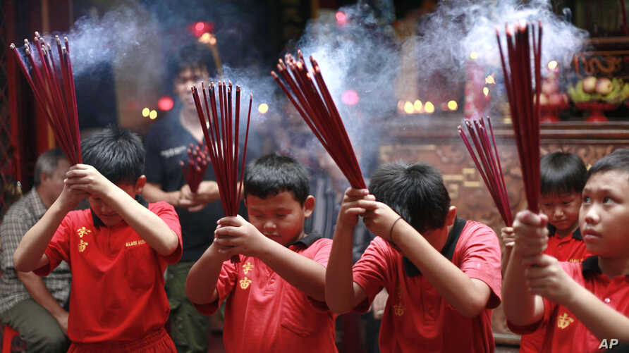Indonesian ethnic Chinese children pray at a temple in the China Town in Jakarta, Indonesia, January 7, 2012.