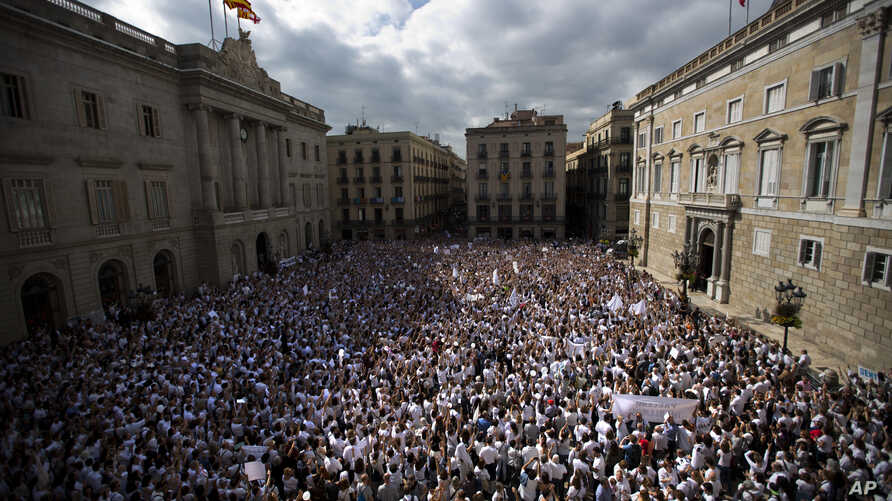 People gather during a protest in favor of talks and dialogue in Sant Jaume square in Barcelona, Spain, Saturday Oct. 7, 2017. Thousands gathered at simultaneous rallies in Madrid and Barcelona in a call for dialogue amid a political crisis caused by