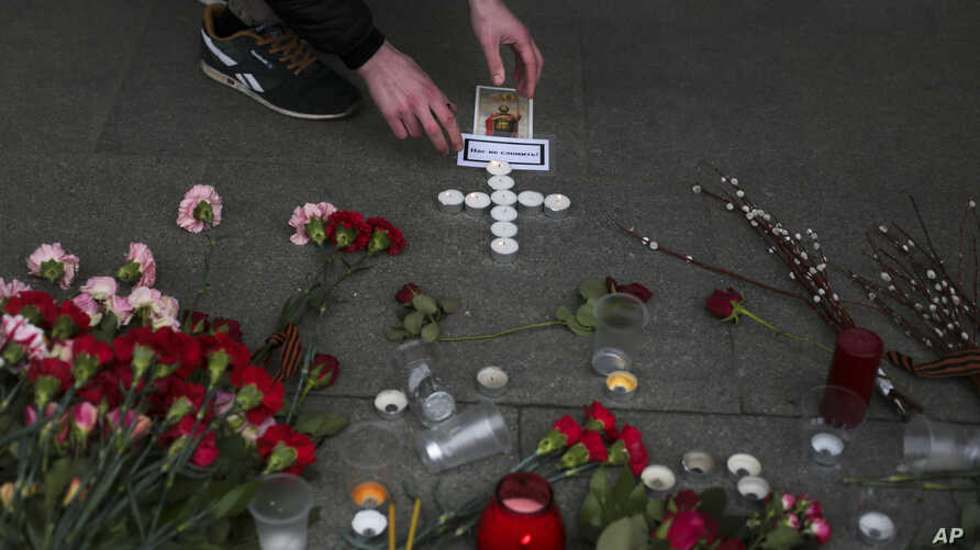 A man lights candles arranged in a form of a cross at a symbolic memorial outside Sennaya subway station in St. Petersburg, Russia, April 4, 2017.