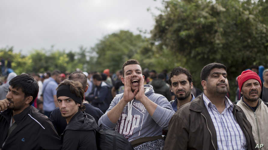 A man shouts while people wait to clear a police line as they entered into Croatia from Serbia, in Babska, Croatia, Sept. 25, 2015.