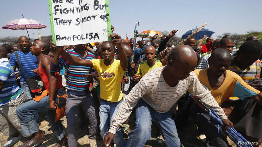 Striking platinum miners march near the Anglo-American Platinum (AMPLATS) mine near Rustenburg in South Africa's North West Province, October 5, 2012.