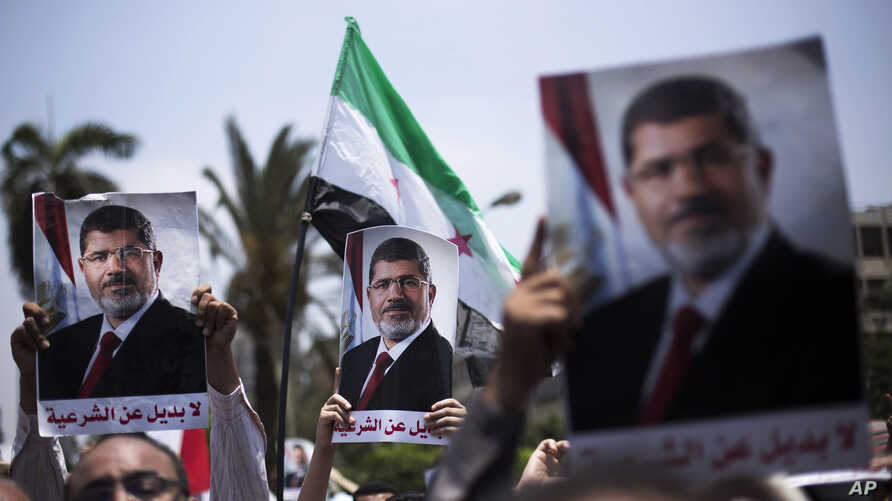 "Supporters hold posters of Egypt's Islamist President Mohammed Morsi during a rally near Cairo University Square in Giza, Egypt, Tuesday, July 2, 2013. Egypt was on edge Tuesday following a ""last-chance"" ultimatum the military issued to Mohammed Mors"