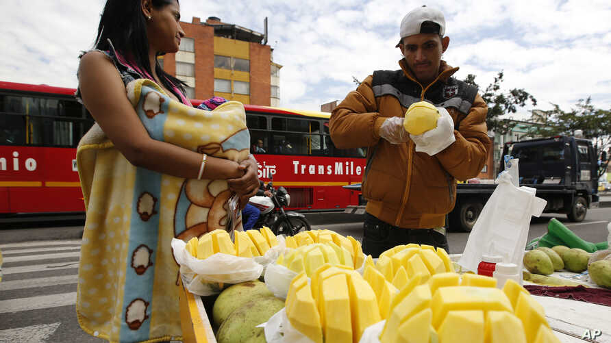 Saraid Valbuena, 20, holds her 4-month-old daughter bundled in a blanket, as her husband Jesus Barrios slices mangoes to sell, in Bogota, Colombia, June 9, 2017.
