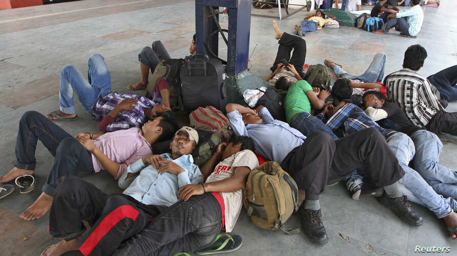 People from India's northeastern states, take a nap at a platform while waiting for the train to board back to their homes at a railway station in the southern Indian city of Chennai, August 17, 2012.