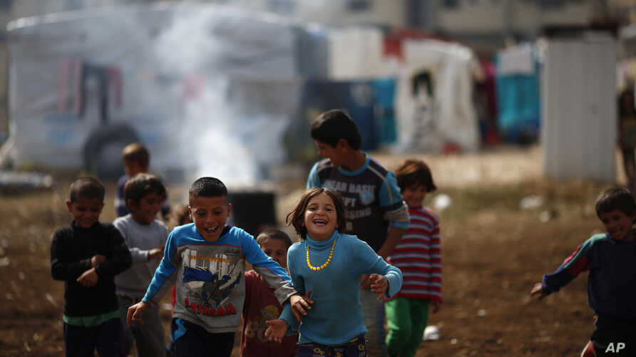 Syrian refugee boys play at a refugee camp in the town of Hosh Hareem, in the Bekaa valley, east Lebanon, October 28, 2015.
