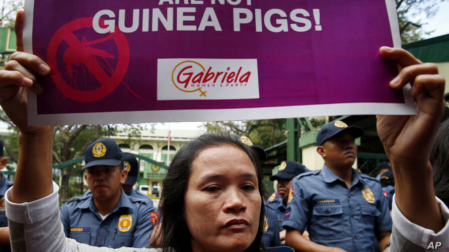 A Mother displays a placard during a rally outside the Department of Health to protest the administration of the anti-Dengue vaccine Dengvaxia which was developed by Sanofi Pasteur, Feb. 7, 2018, in Manila, Philippines.