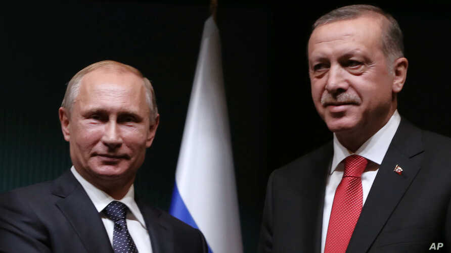 Russian President Vladimir Putin, left, and his Turkish counterpart Recep Tayyip Erdogan shake hands after a joint news conference at the new Presidential Palace in Ankara, Turkey, Dec. 1, 2014.