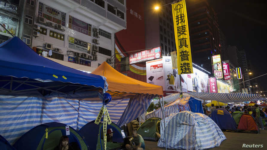 "A large banner reading ""We want universal suffrage"" hung by pro-democracy protesters, is seen on a street light at a main street which they occupied, at Mongkok shopping district in Hong Kong, November 10, 2014."